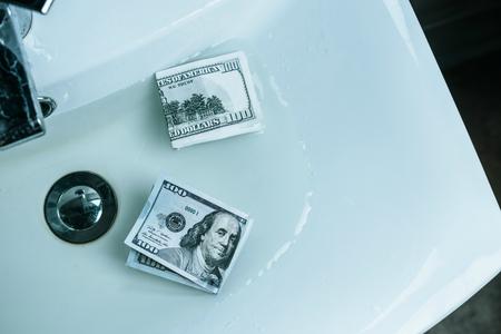 top view of us dollars in water in sink