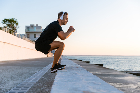 side view of sporty adult man in headphones jumping on parapet on seashore Stock Photo