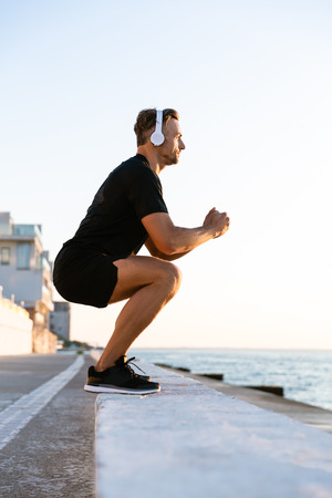 side view of athletic adult man in headphones standing squats on parapet on seashore Stock Photo - 105874158