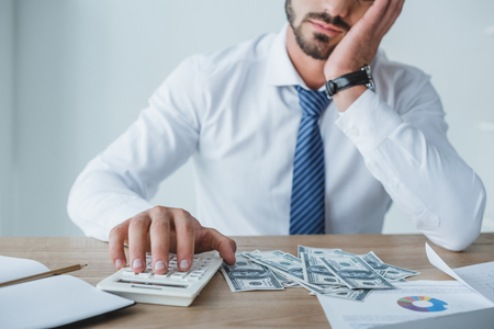 cropped image of tired financier counting money with calculator in office Reklamní fotografie