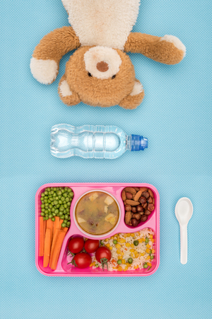 top view of tray with kids lunch for school, teddy bear and bottle of water on blue surface Reklamní fotografie