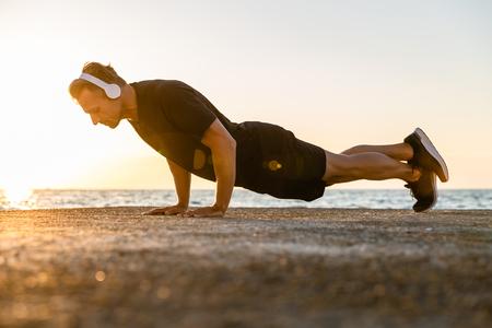 sporty adult man in headphones doing push ups on seashore