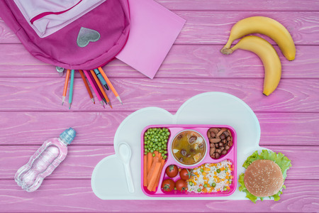 top view of tray with kids lunch for school, pink bag, pencils and bananas on pink table Stock Photo