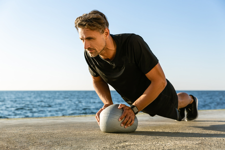 strong adult sportsman doing push ups with fit ball on seashore Stock Photo