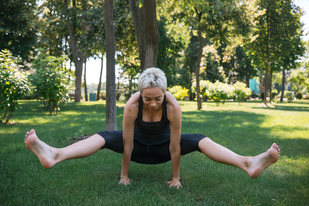 sportive woman practicing yoga and doing positing on hands in park