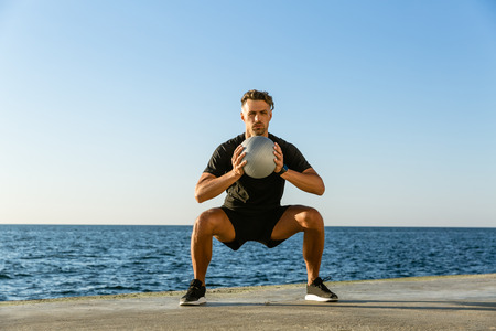 handsome adult sportsman doing squats with fit ball on seashore