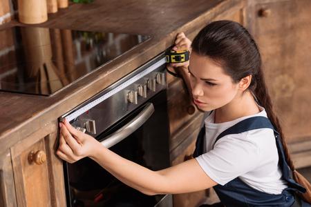 confident young repairwoman measuring width of oven 版權商用圖片