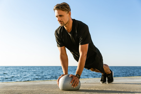 athletic adult man doing push ups with fit ball on seashore