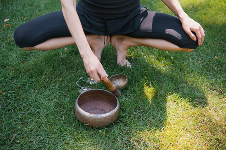 cropped image of woman squatting and making sound with tibetan singing bowls Stockfoto