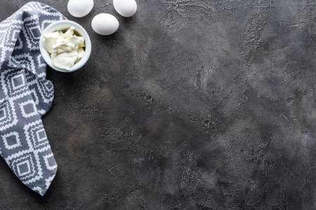 top view of arranged raw chicken eggs, sour cream in bowl and linen on dark grey tabletop