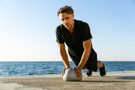 handsome adult sportsman doing push ups with fit ball on seashore and looking at camera Stock Photo
