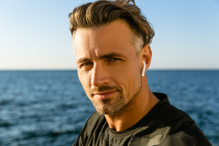 close-up portrait of adult man with wireless earphones on seashore looking at camera