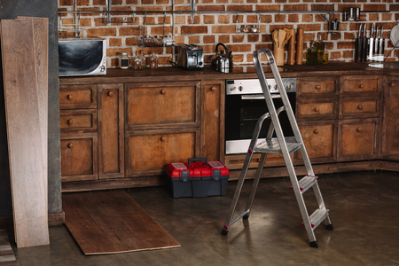 interior of loft style kitchen with stepladder, toolbox and laminate planks on floor Stock Photo - 105874751