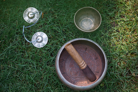 top view of tibetan singing bowls on green grass in park Stockfoto