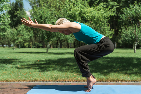 side view of woman practicing yoga on yoga mat in park