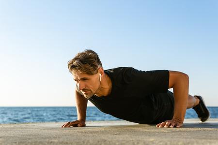 handsome adult sportsman with wireless earphones doing push ups on seashore