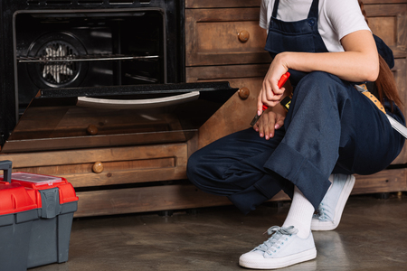 cropped shot of repairwoman with pliers sitting near oven