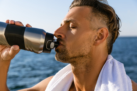 close-up shot of shirtless handsome adult man with towel on shoulders drinking water after workout on seashore