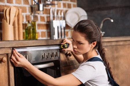 serious young repairwoman measuring width of oven Stock fotó