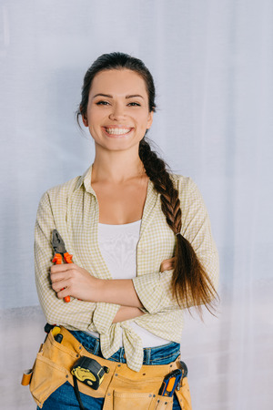 happy young repairwoman with pliers looking at camera Stock Photo
