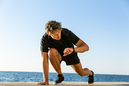 handsome adult sprint runner looking at fitness tracker while standing in start position for run on seashore Stock Photo
