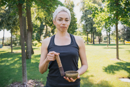 woman making sound with tibetan singing bowl in park and looking at camera
