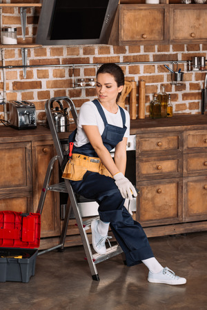 beautiful young repairwoman sitting on stepladder at kitchen Stock Photo