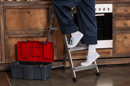cropped shot of repairwoman standing on stepladder at kitchen