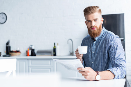 handsome bearded young man holding cup of coffee and looking at camera while reading newspaper at home