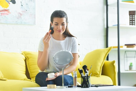 portrait of smiling woman applying face powder while doing makeup at home