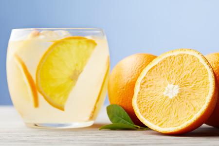 glass of fresh lemonade with ripe oranges on wooden table Banco de Imagens - 105875528