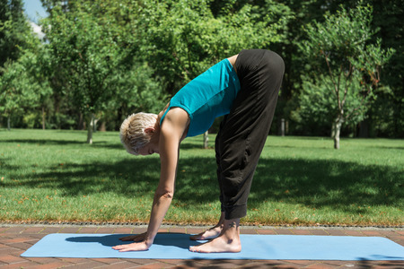woman practicing yoga and doing Halfway Lift pose (Ardha Uttanasana) on yoga mat in park
