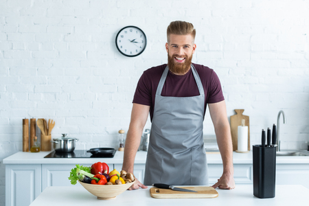 handsome bearded young man in apron smiling at camera while cooking in kitchen