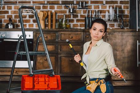 verwirrte junge Reparaturfrau mit Hammer und Zange, die auf dem Boden der Küche sitzt