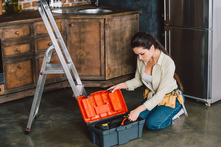 beautiful young repairwoman with toolbox sitting on floor of kitchen Stock Photo