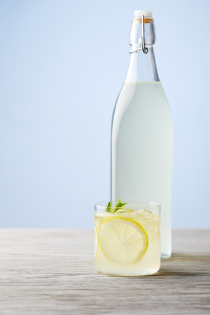 bottle and glass of fresh italian limoncello on wooden surface