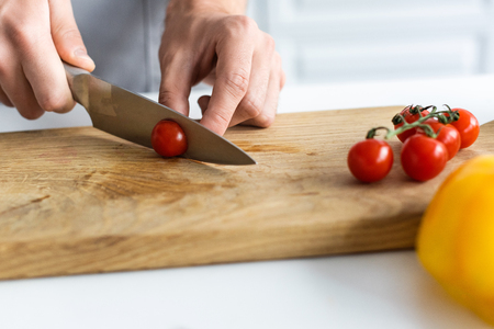 close-up partial view of man cutting cherry tomato on wooden board