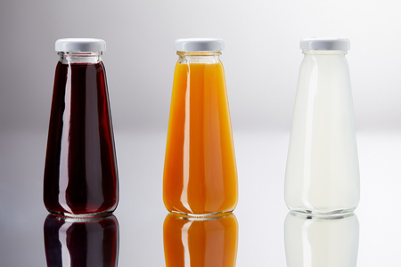 row of bottles of various juice on reflective surface Banco de Imagens