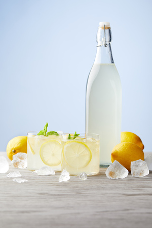 bottle and glasses of traditional italian limoncello on wooden tabletop Stock Photo