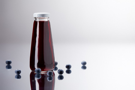 glass bottle of fresh blueberry juice on reflective surface Zdjęcie Seryjne