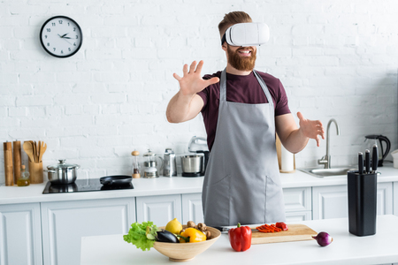 smiling bearded young man in apron using virtual reality headset while cooking in kitchen