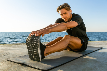 fit adult man with wireless earphones stretching on seashore