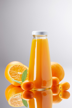 bottle of fresh orange juice with oranges and kumquats on reflective surface