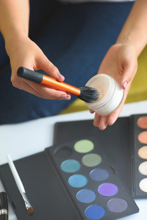 cropped shot of woman holding face powder and makeup brush in hands at home