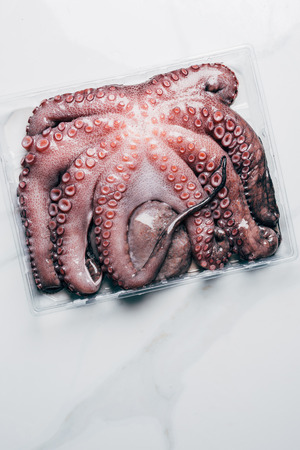 top view of uncooked octopus in plastic container on marble surface Stock Photo