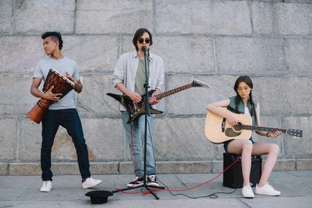 Banda de músicos callejeros jóvenes y felices con guitarras y djembe en la ciudad