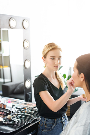 selective focus of young woman getting makeup done by makeup artist Foto de archivo
