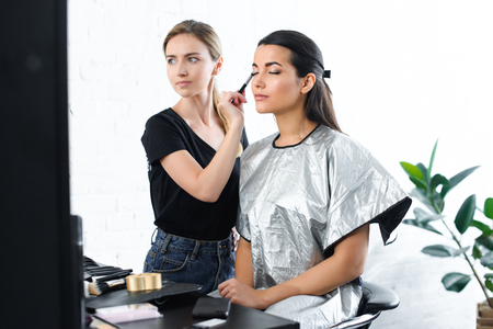 beautiful young woman with eyes closed getting makeup done by makeup artist