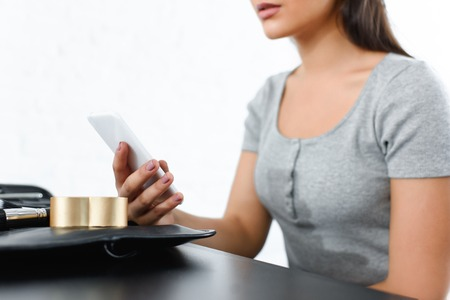 cropped shot of woman using smartphone while sitting at tabletop with cosmetics