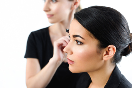 selective focus of young businesswoman getting makeup done by makeup artist 스톡 콘텐츠